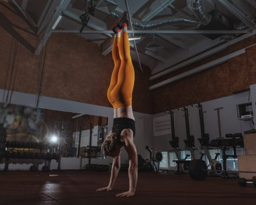 Full length shot of a sportswoman doing handstand at crossfit box gym. Athletic woman walking on her hands at the gym, copy space. Crossfit, balance concept